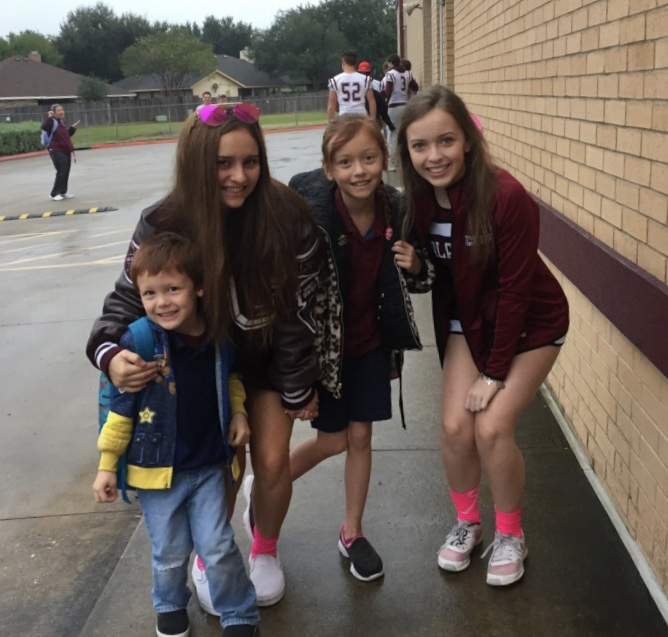 Football Players and Cheerleaders welcome students to school